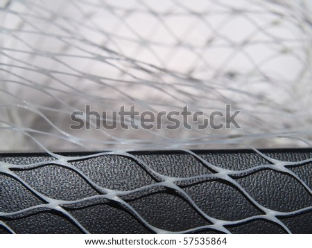 Closeup net and shadow on black leather surface and white background