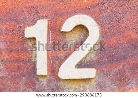 closeup number 12 on red wooden sign board in thailand - stock photo