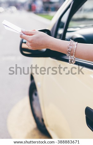 Closeup od woman giving her driver license or ID card - stock photo
