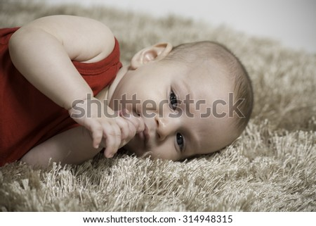 closeup of a baby boy lying on his side  a brown carpet, puts fingers on his mouth - stock photo