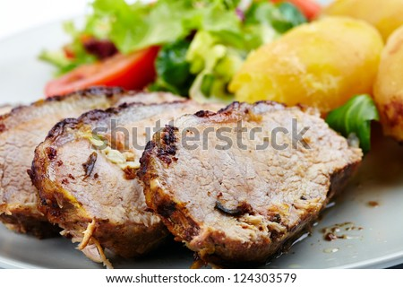 Closeup of a baked tenderloin with garnish of potatoes, lettuce and tomatoes on a plate - stock photo