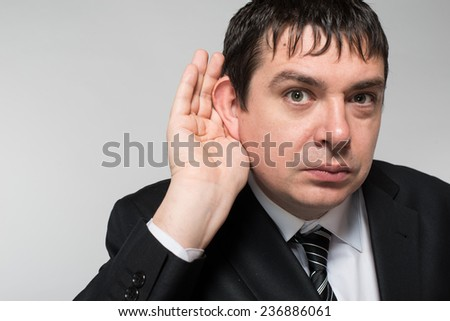 Closeup of a bald businessman with hand behind ear listening closely against gray background - stock photo