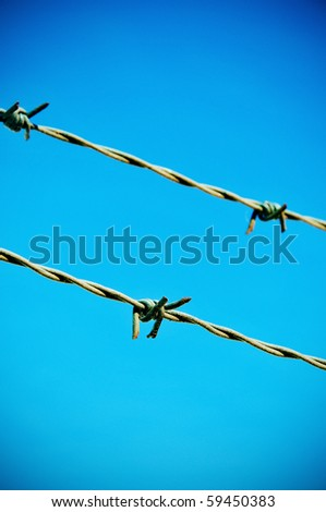 closeup of a barbed wire over the blue sky - stock photo