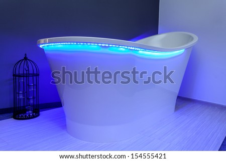 Closeup of a bathtub with blue neon lights
