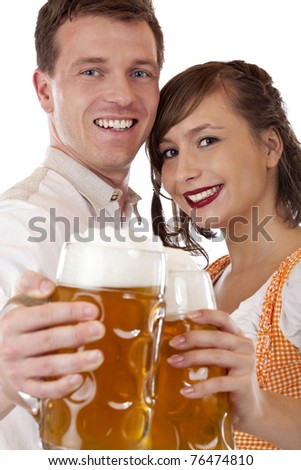 closeup of a bavarian couple holding oktoberfest beer stein and looking happy. Isolated on white background. - stock photo
