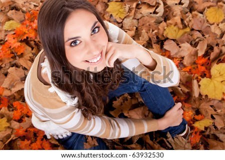 closeup of a beautiful autumn woman in leaves
