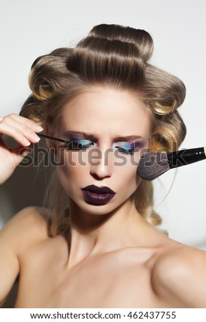 Closeup of a beautiful  fashion model in hair curlers