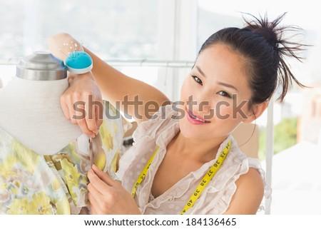 Closeup of a beautiful female fashion designer working on dress at the studio - stock photo