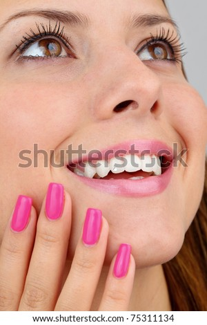 Closeup of  a beautiful lady with healthy smile, dental jewelry, long eyelashes and manicured nails. Intentional shallow depth of field. - stock photo