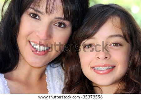 closeup of a beautiful latina woman and her young daughter.