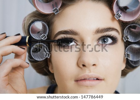 Closeup of a beautiful model in hair curlers applying mascara - stock photo