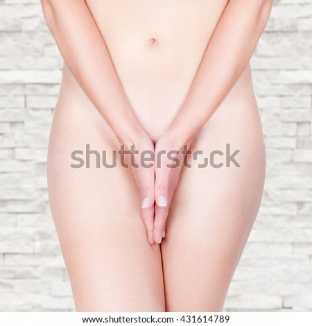 Closeup of a beautiful nude woman hiding her private parts with her hands,  health and hygiene concept, in front of bright marble background - stock photo