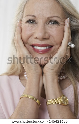 Closeup of a beautiful senior woman with face in hands against white background - stock photo