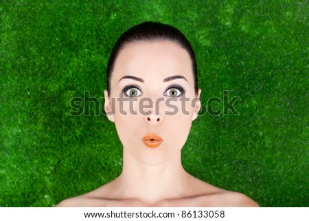 Closeup of a beautiful surprised woman beauty portrait in studio  grass background - stock photo