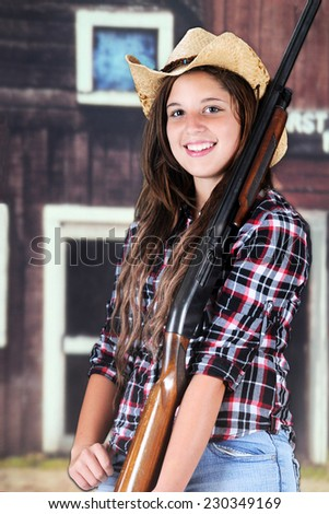 Closeup of a beautiful teen girl happily holding her rifle in front of old western buildings. - stock photo