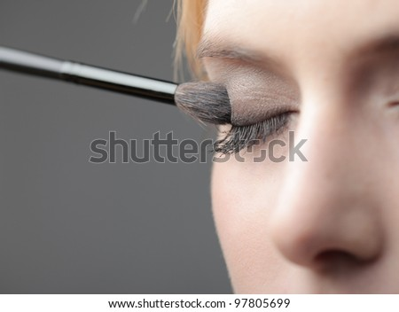 Closeup of a beautiful woman putting on eyeshadow with a brush