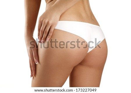 Closeup of a beautiful woman showing perfect buttocks on white