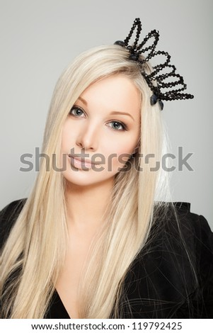 Closeup of a beautiful woman with black crown, indoors - stock photo