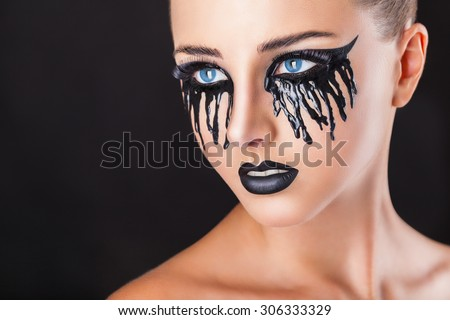 Closeup of a beautiful woman with fantasy makeup with black tears and lips on a black background - stock photo