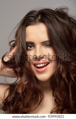 Closeup of a beautiful young woman in a cheerful mood winking