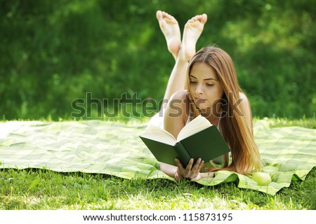 Closeup of a beautiful young woman reading book at park - stock photo