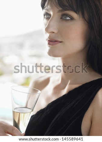 Closeup of a beautiful young woman with champagne glass outdoors - stock photo