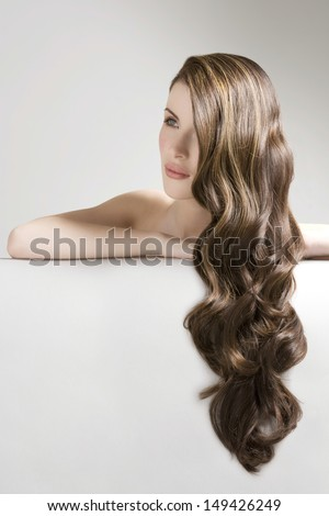 Closeup of a beautiful young woman with long curly brown hair against gray background - stock photo