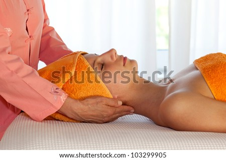 Closeup of a beauty therapist and her young client in orange uniform and towels