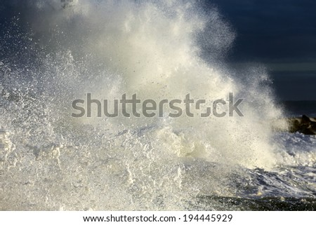 Closeup of a big stormy wave crashing against a pier of the portuguese coast (focus on the lower left foreground ) - stock photo