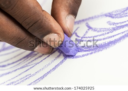 Closeup of a black man's hand drawing a picture with a purple pastel isolated on white background