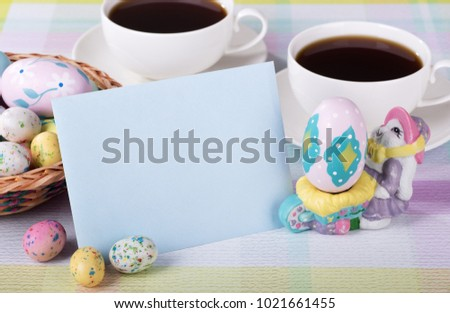 Closeup of a blank envelope with Easter candy and decorated egg and coffee in background