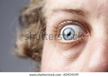 Closeup of a blue eye, of a Caucasian man, showing intricate details of the iris and an expression of shock or fear. - stock photo
