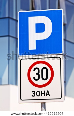 Closeup of a blue park and speed limit signs, building in background - stock photo