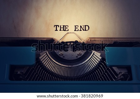 closeup of a blue retro typewriter and the text the end written with it in a yellowish foil - stock photo