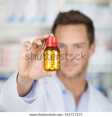 Closeup of a blurred male pharmacist holding out tablets in bottle at drugstore - stock photo
