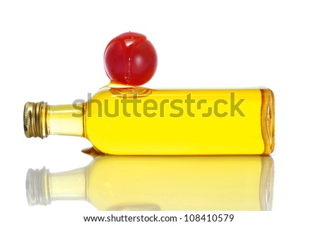closeup of a bottle of olive oil and a tomato on a white background - stock photo