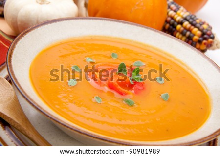 Closeup of a bowl of hot delicious spicy roasted bell pepper pumpkin soup garnished with fresh oregano - stock photo
