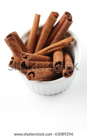 Closeup of a bowl with cinnamon sticks on white background. Shallow dof - stock photo