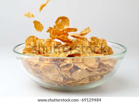 closeup of a bowl with pouring cereal flakes - stock photo