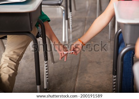 Closeup of a boy and a girl secretly passing down some notes during class - stock photo