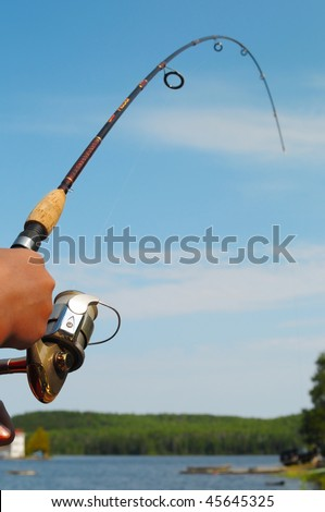 Closeup of a boys hand holding a fishing rod and reel - stock photo