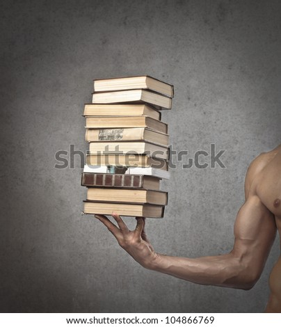 Closeup of a brawny man holding a stack of books in one hand - stock photo