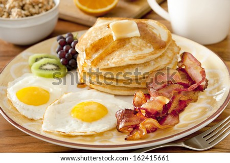 Closeup of a breakfast plate with pancakes, eggs, bacon and fruit. - stock photo