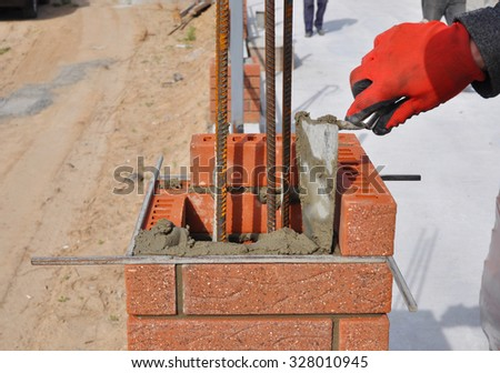 Closeup of a Bricklayer Worker Installing Red Blocks and Caulking Brick Masonry Joints Exterior Wall with Trowel Putty Knife Outdoor. Bricklaying. - stock photo
