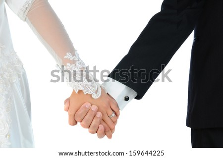 Closeup of a bride and groom holding hands over a white background. Horizontal format. People are unrecognizable. Model Released. - stock photo