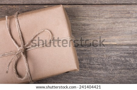 Closeup of a brown package tied with string on a wood background - stock photo