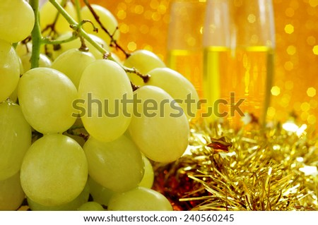 closeup of a bunch of grapes and glasses with champagne in the background for the traditional celebration of the New Year in Spain - stock photo