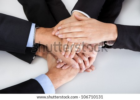 Closeup of a business colleagues with their hands stacked together - stock photo