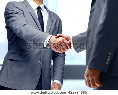 Closeup of a business handshake in office - stock photo