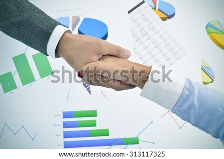 closeup of a businessman and a businesswoman shaking hands above an office desk full of charts - stock photo